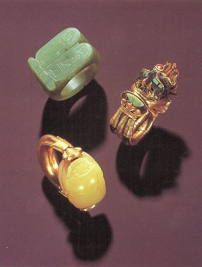 Three of Tutankhamun's Rings: (a) The green nephrite signet shows the King and Min. (b) The three-dimensional bezel is formed from a lapis lazuli scarab flanked by an inlaid falcon and moon barque on a cartouche-shaped base. The inlays are green jasper and glass. (c) The scarab bezel of the gold ring is of chalcedony; the underside shows Thoth and the udjat. ~via paralyze