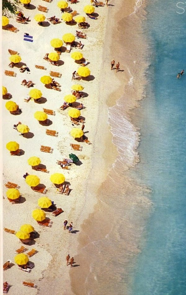 A pristine white sand beach peppered with yellow umbrellas