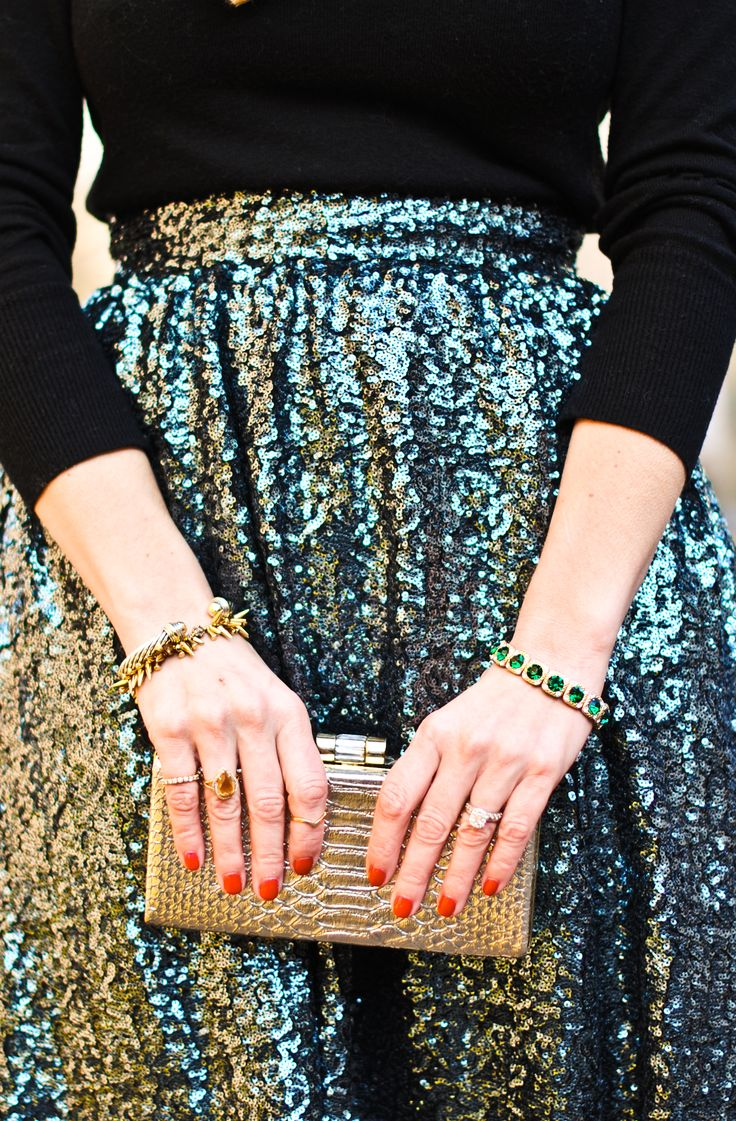 Sparkling sequined skirt with black sweater and gold clutch
