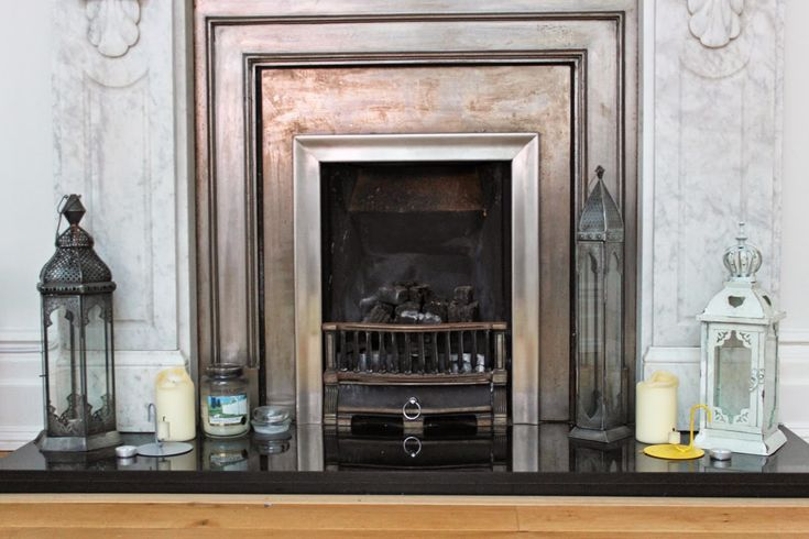 Beautiful metallic fireplace. I love the large glass and brass candle holders placed on the arth.