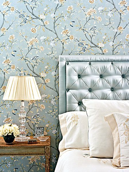 Glamorous Hollywood style tufted headboard against floral and branch wall covering.