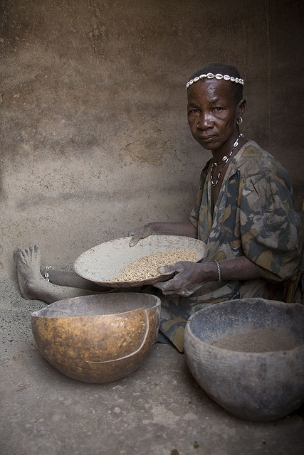 Africa | A woman from the Tamberma Valley cleaning and sorting grain  | © Christopher Herwig