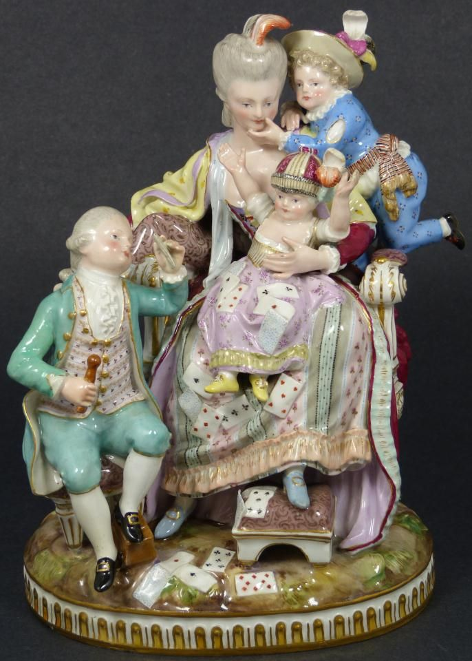Antique Meissen German porcelain group figure depicting a woman sitting in a seat with three children. The children are playing cards. 19th century, 8.75 inches in height