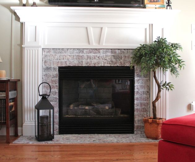 white washed brick fireplace with a white mantle def