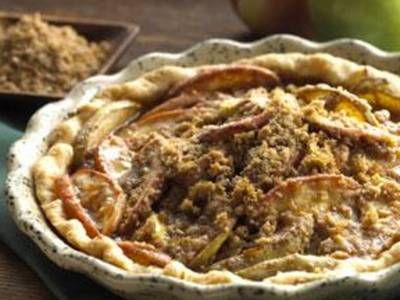 Spiced apple pie with a sweet thick glaze and crumbles over the top.