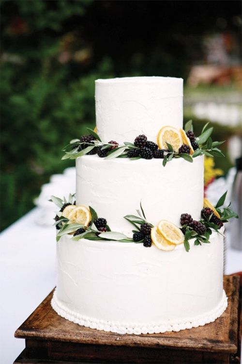 Elegant and simple wedding cake with blackberries and lemons