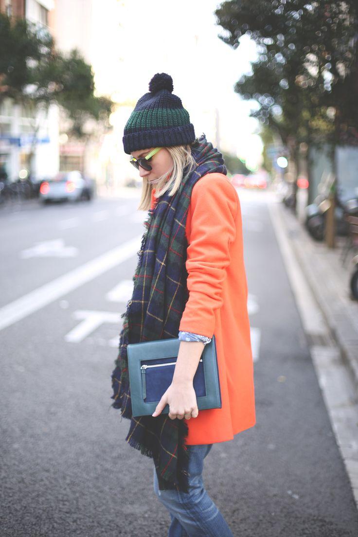 オレンジ色のコートとマフラーとニット帽