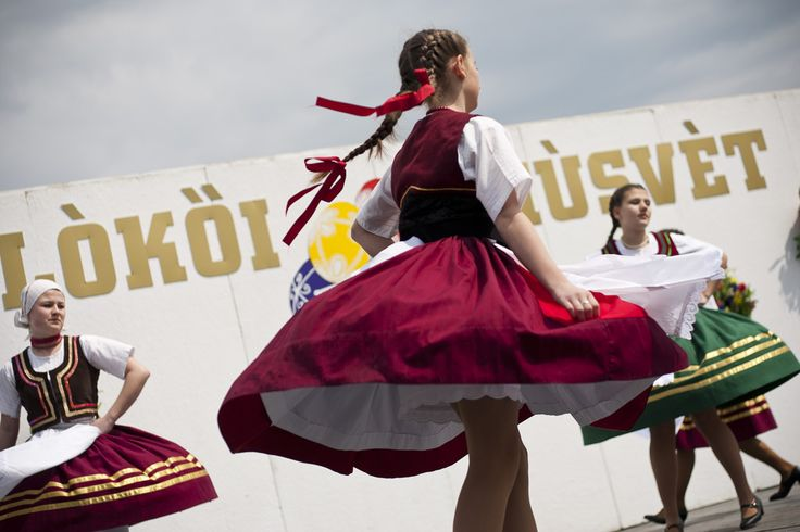 Girls performing traditional Hungarian folk dancing on an open-air stage.