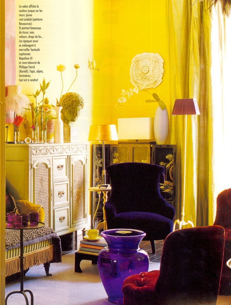 Bohemian Style Living Room With Lemon Yellow Walls And A Violet Purple Upholstered Chair