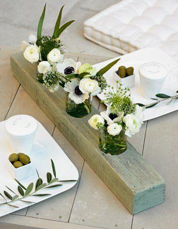 Un centre de table comme un tryptique de fleurs ou de bougies dans une poutre en bois