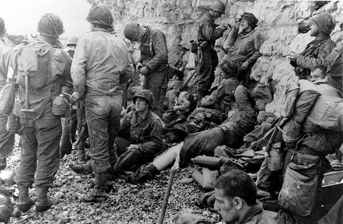 Sous le Wn 60 au pied de la falaise de Colleville sur Mer, Omaha Beach secteur Fox Red à droite de Fox Green et de F-1  Secteur du 3rd Bn du 16th RCT de la 1st US ID, Ces soldats sont à l'abri du feu allemand, les infirmiers débarqués avec eux traitent les blessés légers.  L'homme au centre blessé à l'œil appartient à la 29th US ID (Blue and Grey) le patch d'épaule n'est pas censuré ; sans doute un homme des 4 sections de la E/116th IR ayant échoué dans ce secteur (au lieu d'Easy Green).