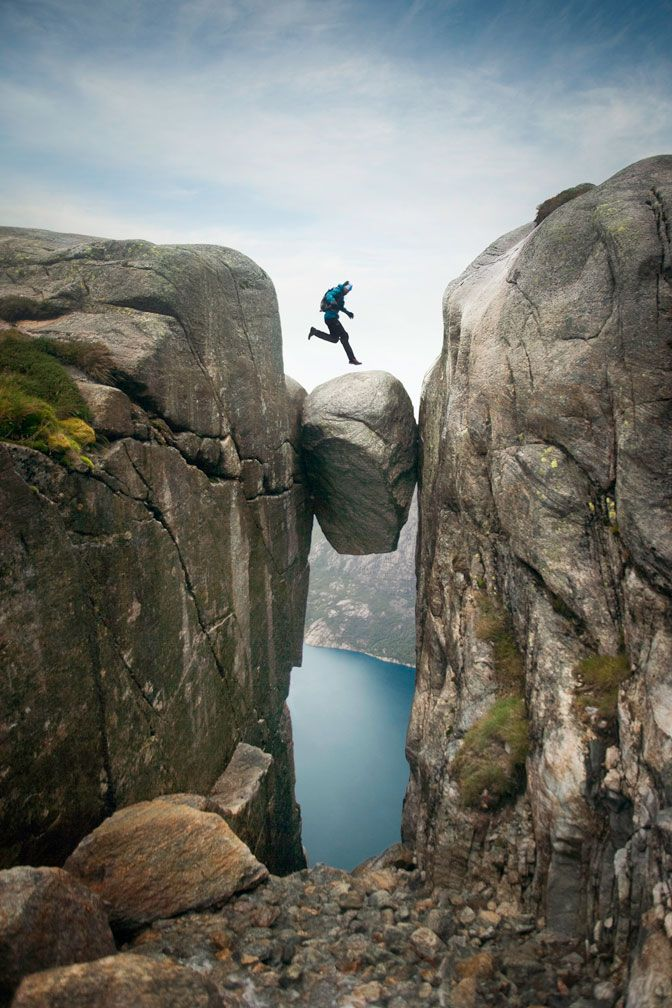 crazy cool photo!! Jumping Kjeragbolten by Caterina Bernardi: Kjeragbolten is a 5 m³ boulder wedged into a crevasse at the beginning of Lysfjorden, Norway and is balanced 1000' above the fjord below. A popular destination for base jumping, there have been 20 fatalities between 1994 - 2008. This amazing, award winning image was captured as a young adventurer jumped up and down the boulder in the rain as if he was on solid ground.