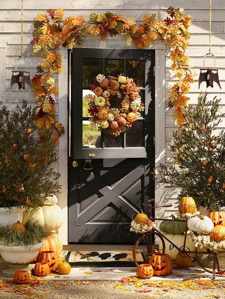 fall door complete with garland, wreath and pumpkins and gourds displayed to welcome guests...