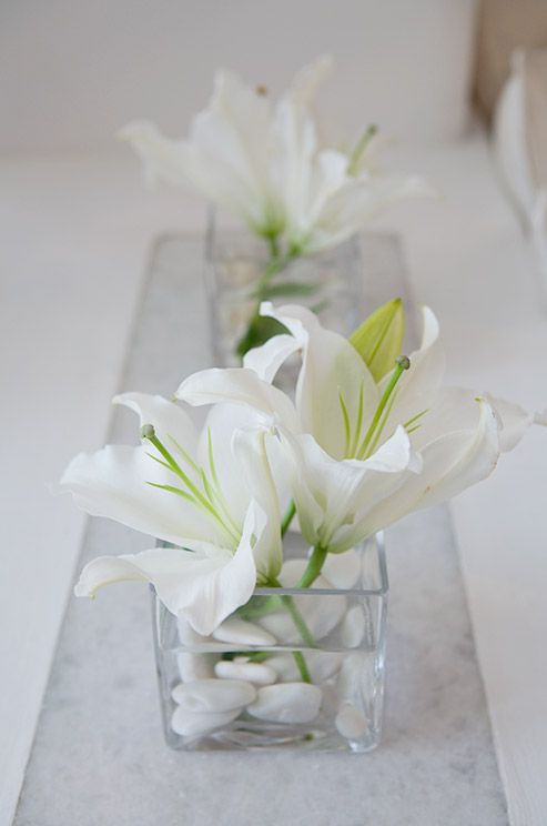 A glass container holding a couple of white lilies and white stones makes for elegant and minimal decor.