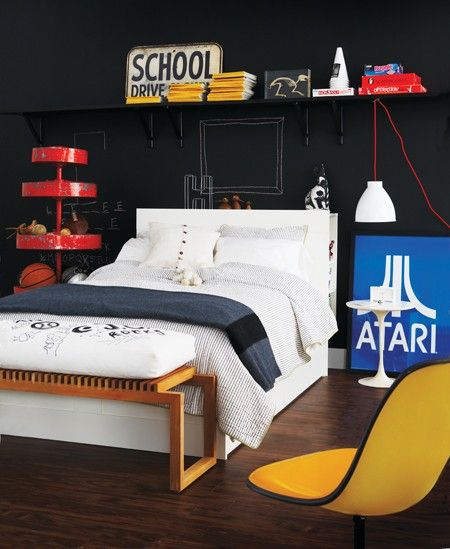 "Creative Kids' Bedroom    Create a bold accent wall with black chalkboard paint, so kids can ""redecorate"" their room.    Black shelves disappear against the dark backdrop, making their contents appear to float. Conversely, bright colours pop: a red vintage store display has tiers of rotating shelves for keeping the floor clear of gear."