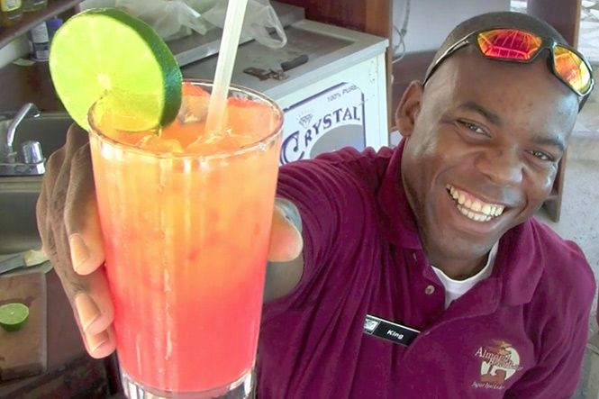 Belize Rum Punch Recipe        2 shots light rum      2 splashes grenadine syrup      1 shot dark rum      top with pineapple juice      1 shot orange liqueur      1 shot sweet and sour mix      1 shot cream of coconut    Cheers!