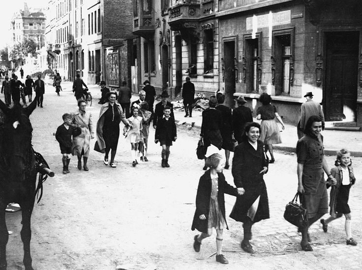 German mothers walk their children to school through the streets of Aachen, Germany, on June 6, 1945, for registration at the first public school to be opened by the U.S. military government after the war. (AP Photo/Peter J. Carroll)