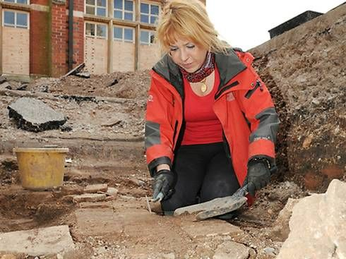 A member of the Richard III Society, examining a shred of medieval tile at the excavation site