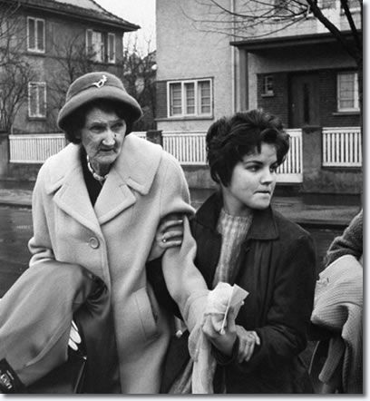 Elvis Presley's grandmother Minnie Mae Presley being led to her car by the singer's 16-yr-old girlfriend Priscilla Beaulieu in front of his house as she prepares to see him off on plane for his return to the US.