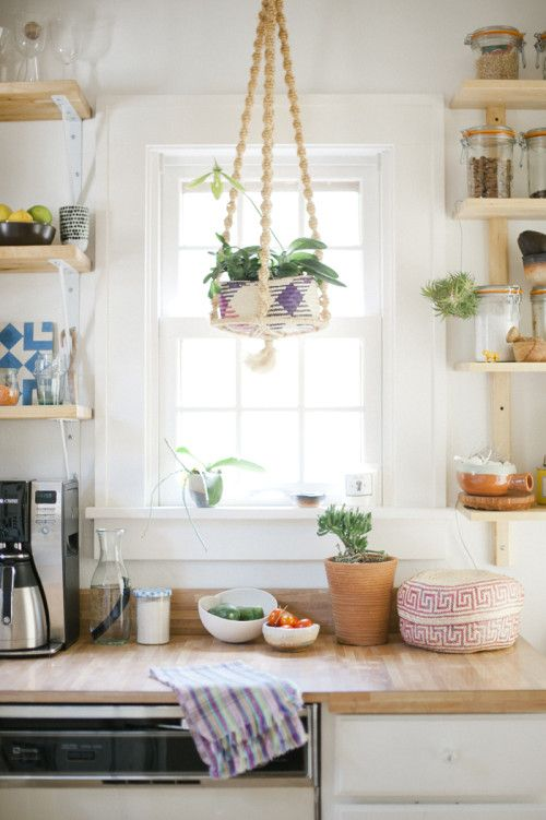 Wooden counters and greenery make for a homey kitchen design