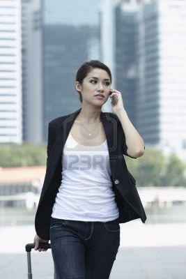 Diese Frau kann beides – telefonieren UND Rollkoffer ziehen.