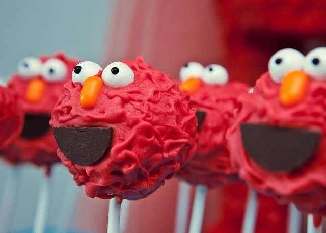 Elmo cake pops- you can buy red dipping chocolate at the store. Then, before the chocolate is totally dry, use half of a chololate gold coin for the mouth, a jelly bean for the nose, and two halved of a mini marshmallow for the eyes.  | Kara's Party Ideas