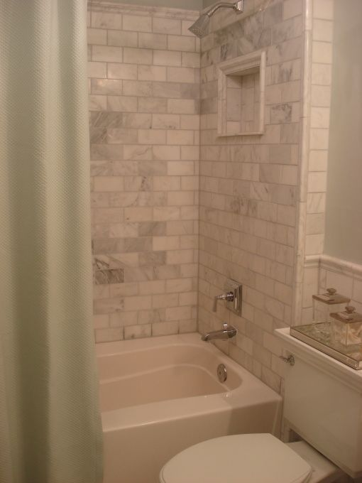 small builder grade bathroom upgraded with marble subway tiles on