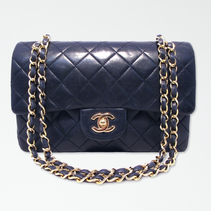 This beautiful, classic Chanel handbag features a stunning midnight blue quilted leather exterior, trimmed with gold hardware and the signature ...