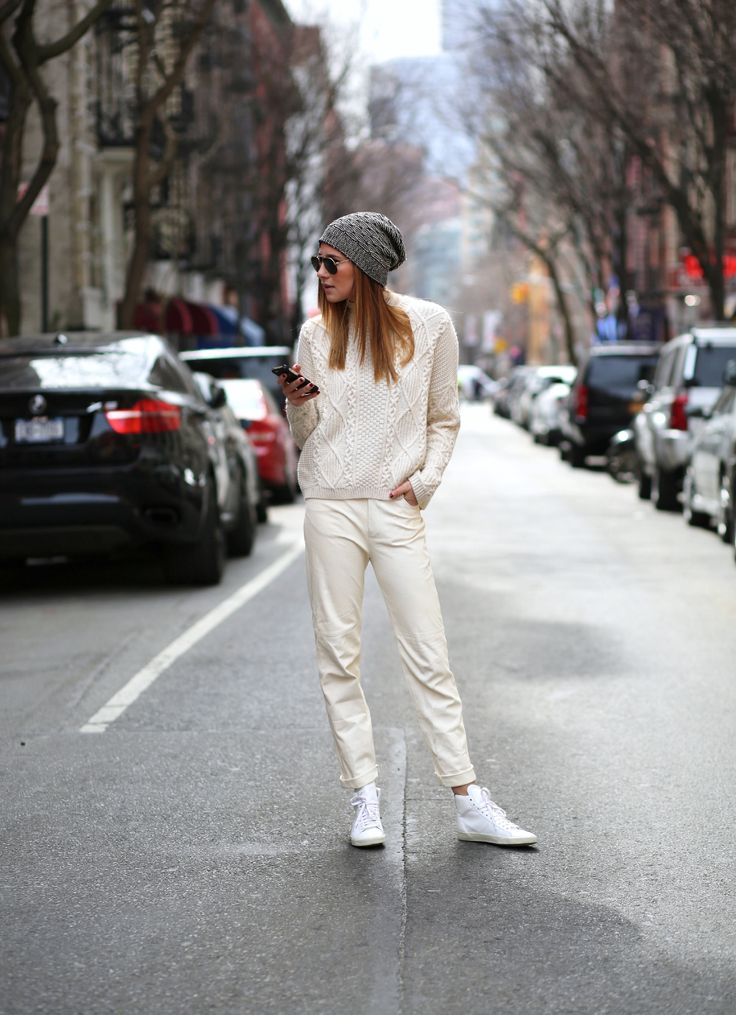 Danielle Bernstein of We Wore What adds texture to an all white look with a cable knit sweater // #StreetStyle #Fashion