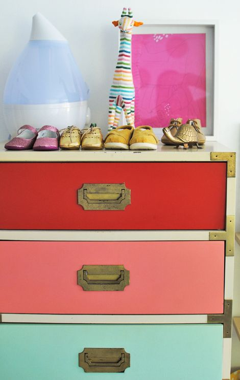 vintage dresser with seven different colored drawers and gold hardware!