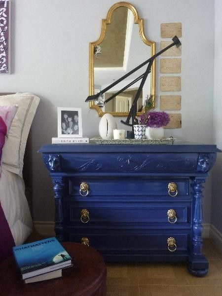 lovely gold antique mirror with navy cabinet in a bedroom