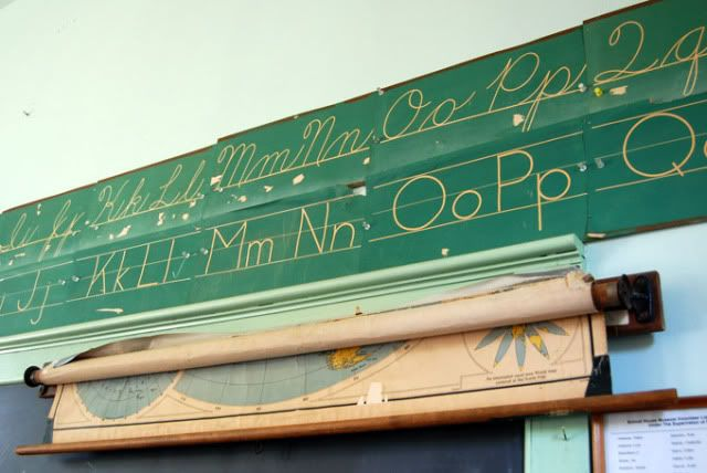 Cursive                                                            writing guides                                                            above the                                                            chalkboard and                                                            pull-down                                                            maps.