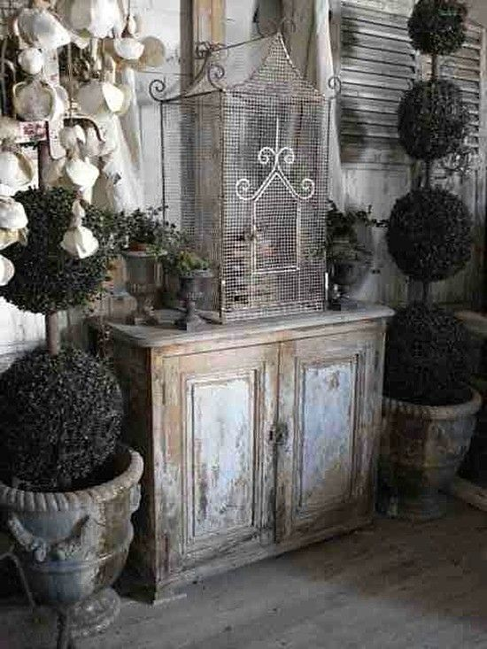Old weathered cabinet, birdcage & topiaries.