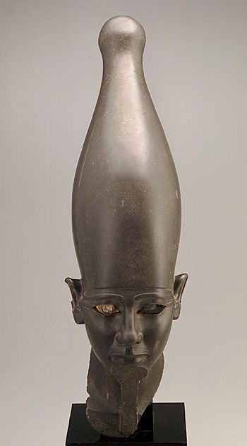Head of a Pharaoh, ca.2675-2130 BCE, Old Kingdom, Dynasty 5 or 6. Stone and copper, h: 73.0 cm. The headgear and moustache identify the figure as an Egyptian pharaoh; the tall crown with the rounded top, known as the White Crown, signified rule over southern Egypt. Broken at the neck, the head originally belonged to a full, probably standing, statue of the kind placed in tombs to serve as eternal images of the deceased