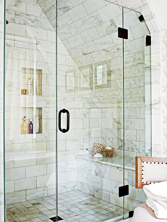 Soothing Shower  A spacious marble shower nestles beneath a sloping roofline. A pair of recessed wall niches streamlines shower storage, offering ample space for shower necessities without the bulk of a caddy. A built-in shower bench provides a perch for shaving. The shower's unpolished marble achieves a warm and soothing look.