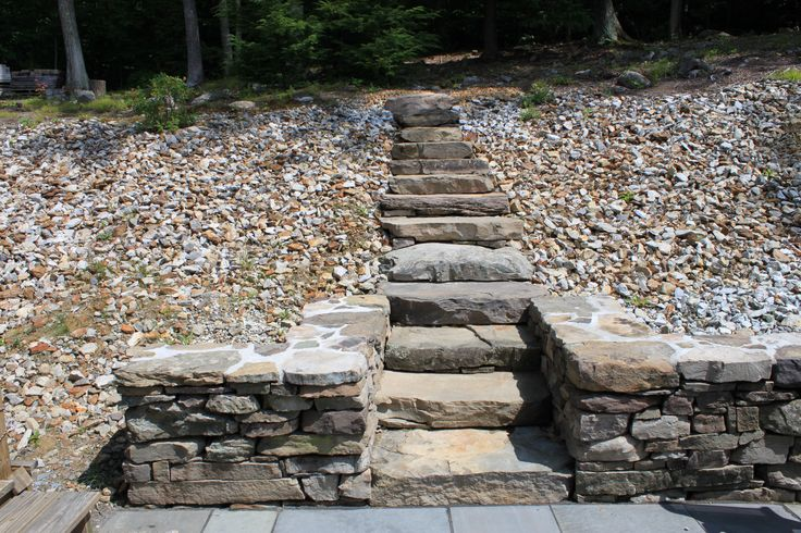 backyard stone steps built into a hill and connected to a stone wall