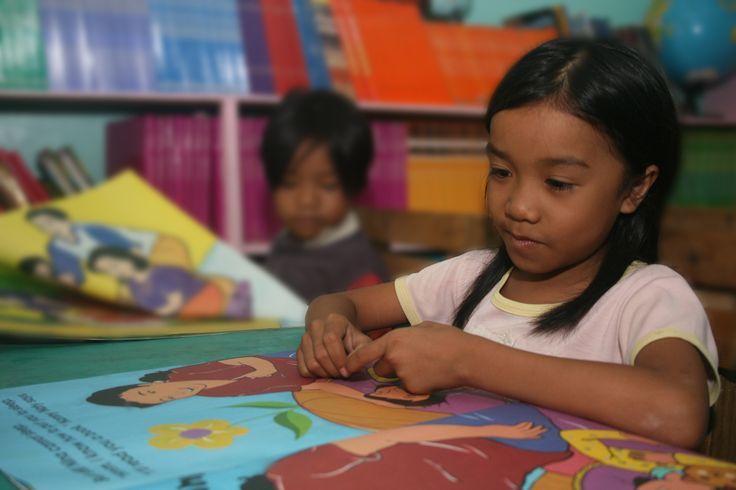 Image of young girl in mindanao philippines reading a book donated by