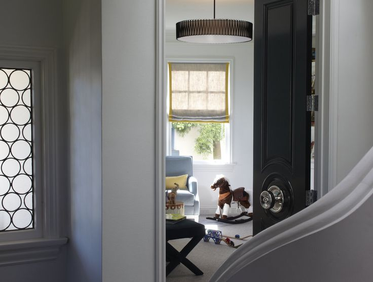 An ebony-painted door accented with an oversize doorknob lends a glamorous entrance to the playroom.