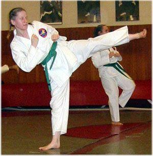 female green-belt doing side kick Tae Kwon Do is a Korean martial art