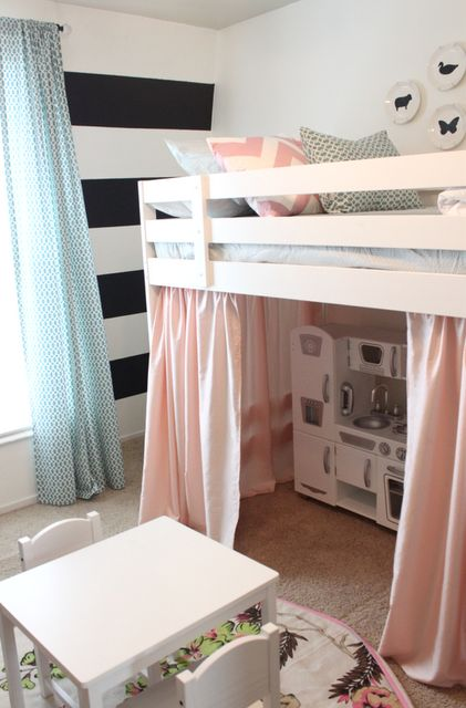 precious little girls room with a loft bed, pink curtains, black and white striped walls, play kitchen
