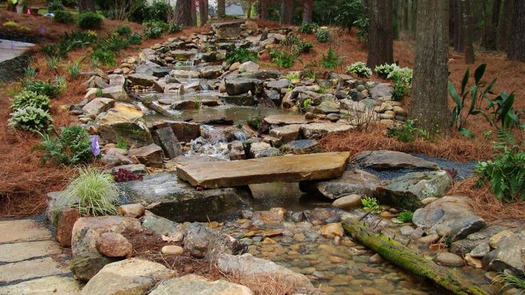Man made mountain stream with pond, patio,fire pit, playground, plants ...