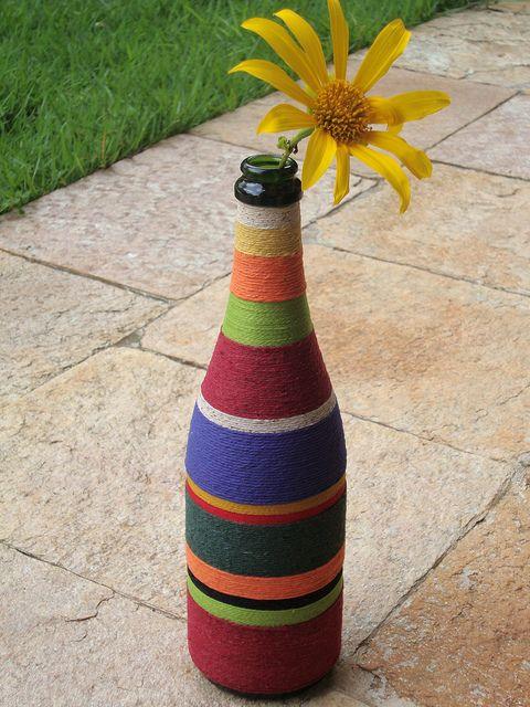 A garrafa de vidro que ia para o lixo se transforma em um lindo vaso para flores simplesmente sendo envolvida em fios de crochê ou de tricô.