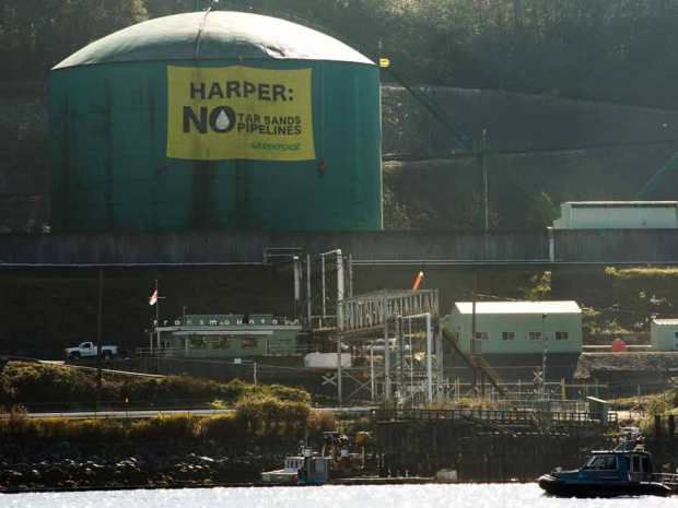 Greenpeace activists hang a large banner off of one of the oil storage containers at the Kinder Morgan facility in Burrard Inlet in Burnaby, B.C. last year.