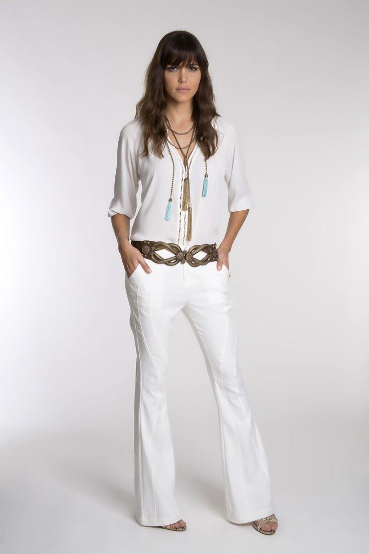 A blusa com entremeios com ponto palito e a calça flare com recortes formam um look total white, que fica ainda mais sofisticado com o cinto em ouro velho com tachas e os colares de tassel.