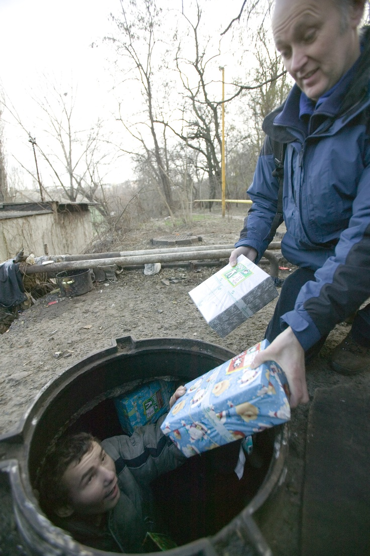An image of a child receiving an Operation Christmas Child shoe box:  Street children in Ukraine - living in holes in the ground - c2006. This is why I continue to fill  boxes.