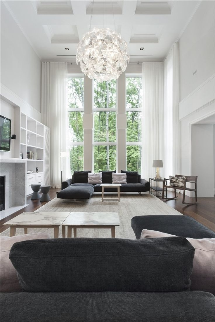 casual living room in neutral colors. iights lamps chandeliers. globe chandeliers.extra tall windows.