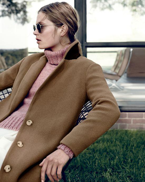 J.Crew women's stadium-cloth topcoat, Ray-Ban retro round sunglasses, and chunky turtleneck sweater.