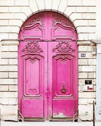 ...a pink wooden door with beautiful detailing.