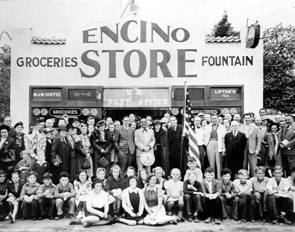 Encino Post Office dedication day, circa 1935-1942. Some of Encino's celebrities are visible in the picture. At center holding a white hat is Al Jolson. The man to his left, next to the flag is the actor Edward Evertt Horton. To the right of the flag is Peter Amestoy. The second person to the right of the flag is the actor Phil Harris and two over from him on the right, smiling with an open collared shirt is the actor Don Ameche. West Valley Museum. San Fernando Valley History Digital Library.