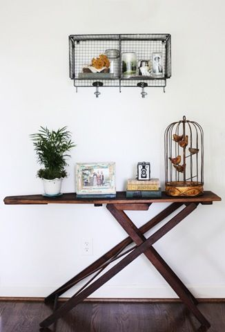 Cool idea - a vintage wooden ironing board as a console table.... Not really into the metal shelf thing on the wall though.